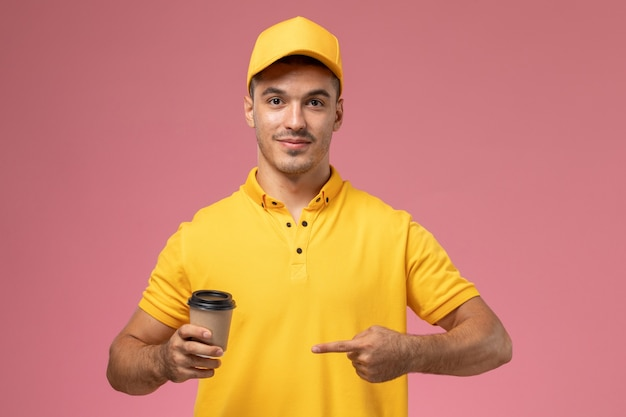 Front view male courier in yellow uniform holding coffee delivery cup on pink background