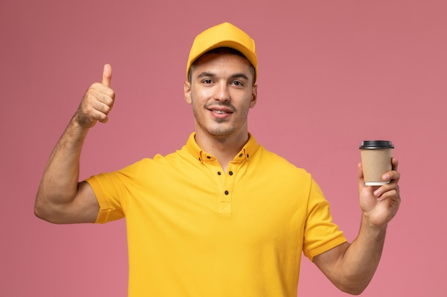 Front view male courier in yellow uniform holding coffee delivery cup on the pink background