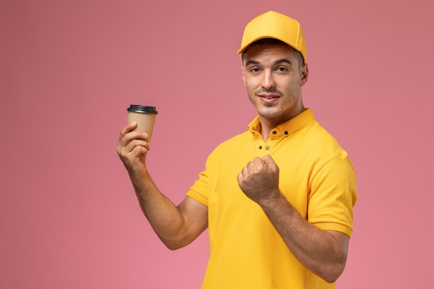 Front view male courier in yellow uniform holding coffee delivery cup on pink desk