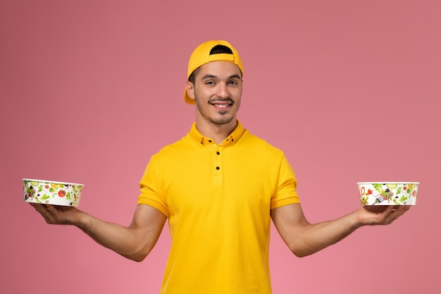Front view male courier in yellow uniform holding delivery bowls on the pink background.