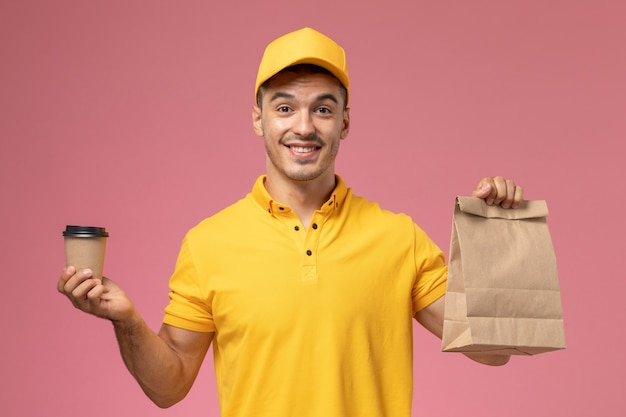 Front view male courier in yellow uniform holding delivery coffee cup and food package on pink desk