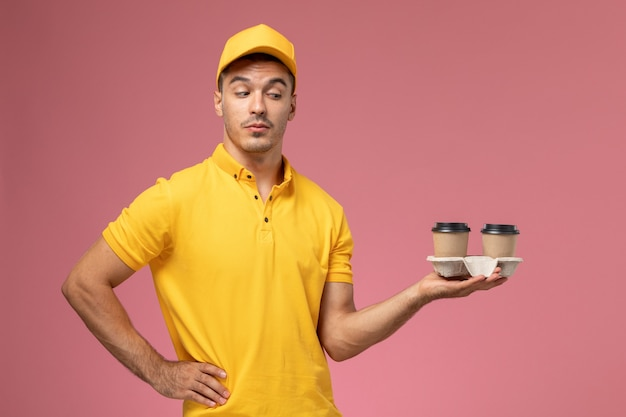 Front view male courier in yellow uniform holding delivery coffee cups on light-pink background