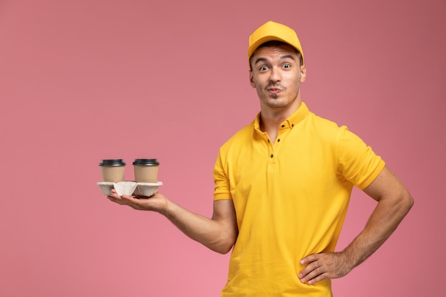 Front view male courier in yellow uniform holding delivery coffee cups on the light-pink background
