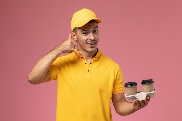 Front view male courier in yellow uniform holding delivery coffee cups phone call posing on light-pink background