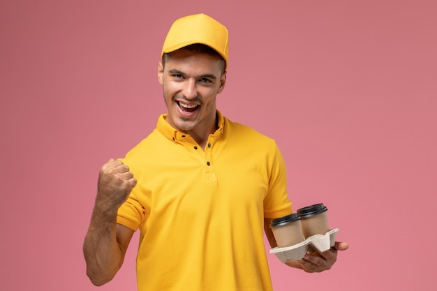 Front view male courier in yellow uniform holding delivery coffee cups and rejoicing on pink background