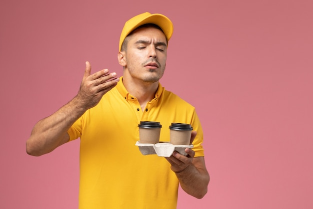 Front view male courier in yellow uniform holding delivery coffee cups smelling them on light-pink background