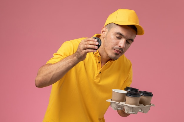 Front view male courier in yellow uniform holding delivery coffee cups smelling them on the pink desk