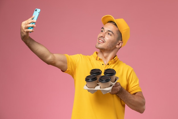 Front view male courier in yellow uniform holding delivery coffee cups taking photo with them on pink desk
