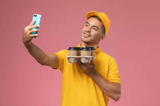 Front view male courier in yellow uniform holding delivery coffee cups taking selfie on pink desk