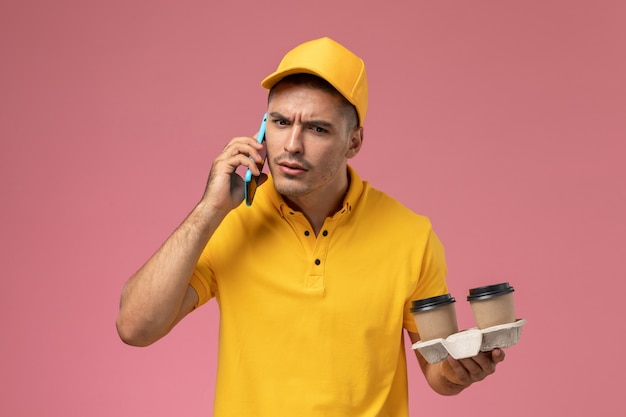 Front view male courier in yellow uniform holding delivery coffee cups talking on the phone on the pink background