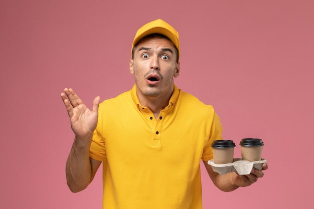 Front view male courier in yellow uniform holding delivery coffee cups with shocked expression on light-pink desk