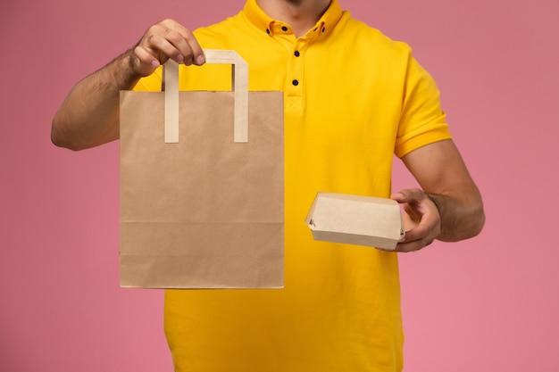 Corriere maschio di vista frontale in uniforme gialla che tiene i pacchetti di cibo di consegna sullo sfondo rosa chiaro.