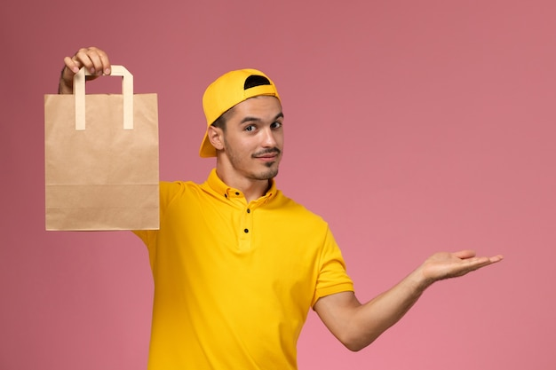 Front view male courier in yellow uniform holding delivery paper package on light pink background.