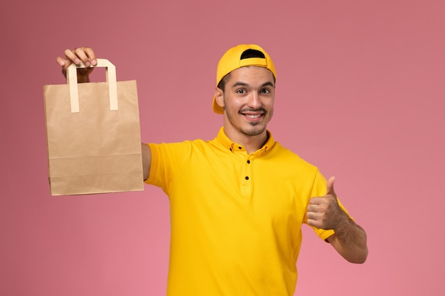 Front view male courier in yellow uniform holding delivery paper package smiling on light pink background.