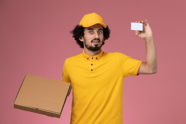Front view male courier in yellow uniform holding food delivery box and card on the pink wall