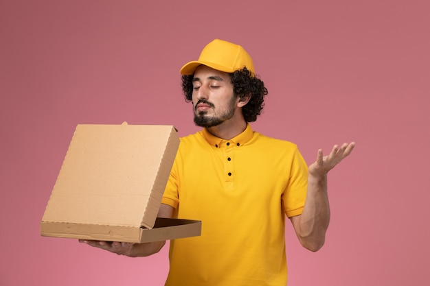 Front view male courier in yellow uniform holding food delivery box on the light-pink wall
