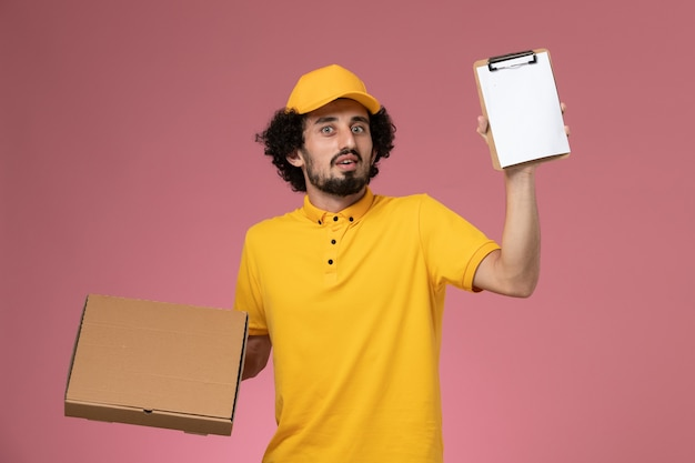 Front view male courier in yellow uniform holding food delivery box and notepad on light pink wall