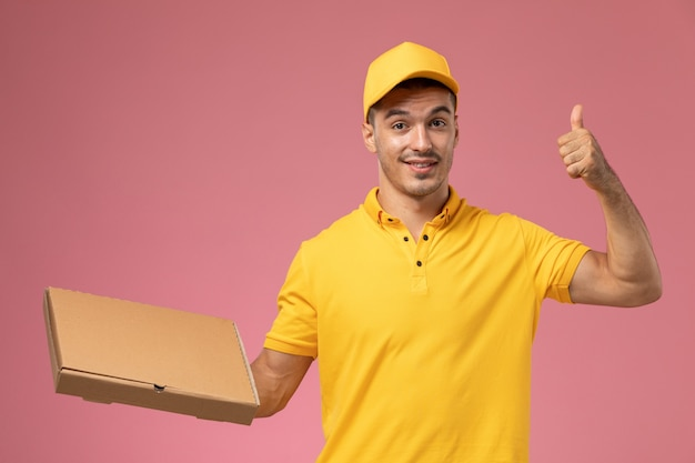 Front view male courier in yellow uniform holding food delivery box on pink background