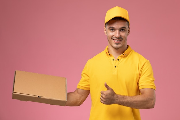 Front view male courier in yellow uniform holding food delivery box on the pink background