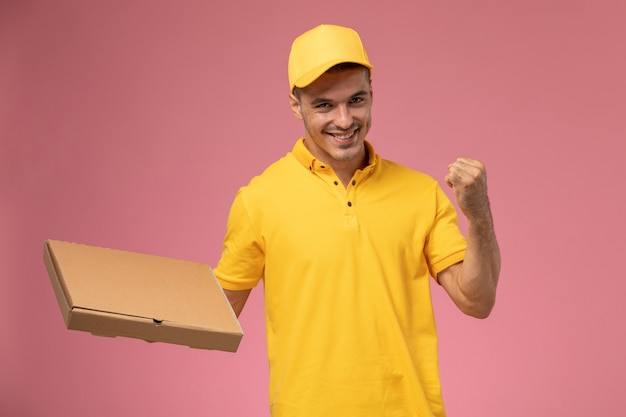 Front view male courier in yellow uniform holding food delivery box and rejoicing on the pink background