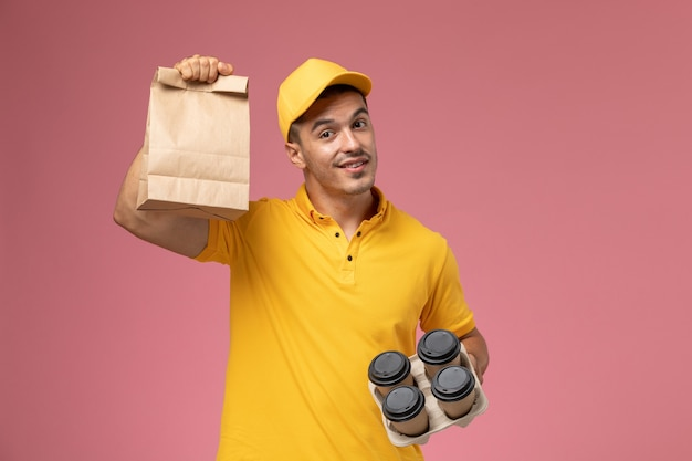 Front view male courier in yellow uniform holding food package and delivery coffee cups on pink background