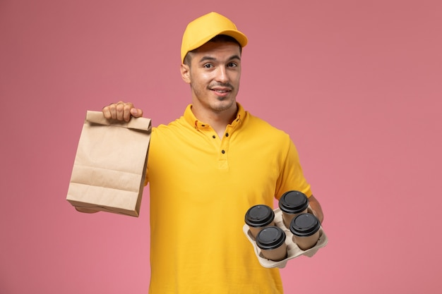 Front view male courier in yellow uniform holding food package and delivery coffee cups on the pink background