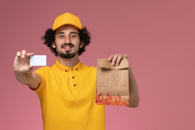Front view male courier in yellow uniform holding food package and plastic card on the pink wall