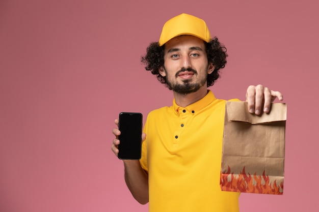 Front view male courier in yellow uniform holding food package and smartphone on the pink wall