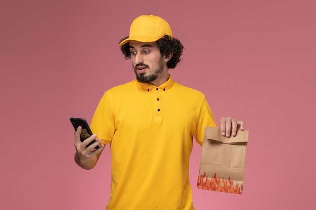 Front view male courier in yellow uniform holding food package and using phone on the pink wall