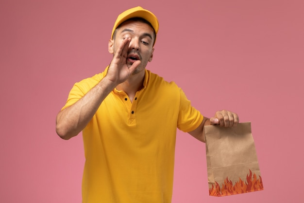 Front view male courier in yellow uniform holding food package whispering on the pink background