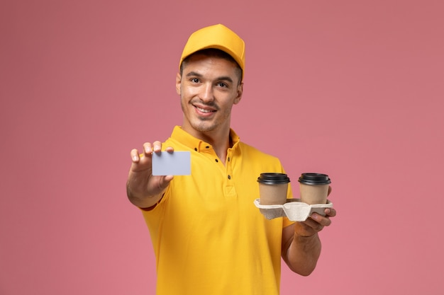 Front view male courier in yellow uniform holding grey card and delivery coffee cups on light-pink background