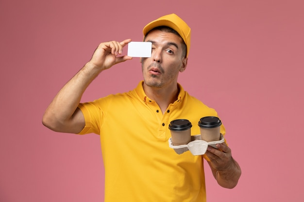 Front view male courier in yellow uniform holding grey card and delivery coffee cups on pink background