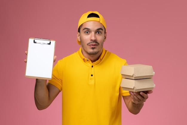Corriere maschio di vista frontale in uniforme gialla che tiene piccoli pacchetti di cibo e piccolo blocco note su sfondo rosa chiaro.