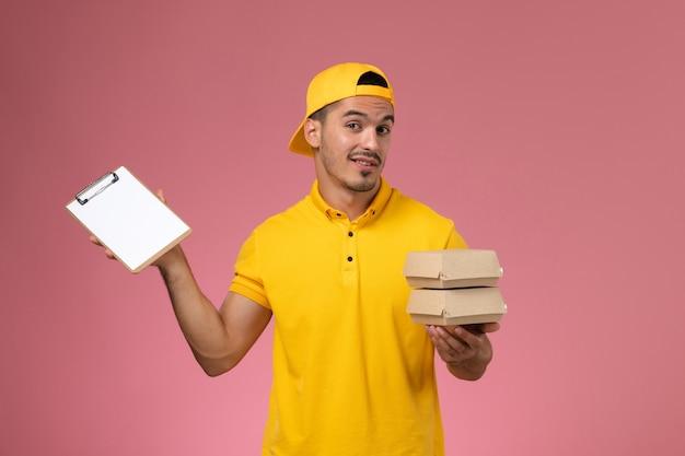 Corriere maschio vista frontale in uniforme gialla che tiene piccoli pacchetti di cibo e blocco note pensando sullo sfondo rosa chiaro.