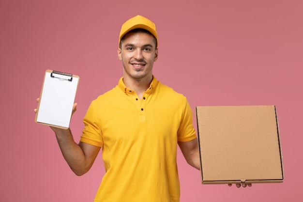 Front view male courier in yellow uniform holding notepad and food delivery box with smile on pink desk