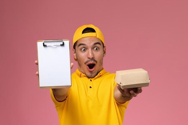 Corriere maschio di vista frontale in blocco note giallo uniforme della tenuta e piccolo pacchetto di cibo su sfondo rosa chiaro.