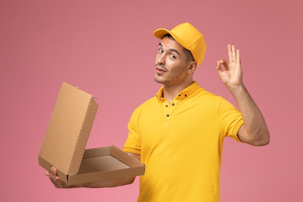 Front view male courier in yellow uniform holding and opening empty food delivery box on pink desk