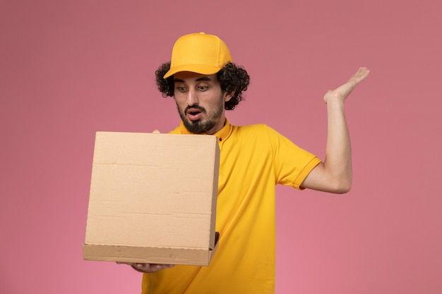 Front view male courier in yellow uniform holding and opening food delivery box on the light-pink wall