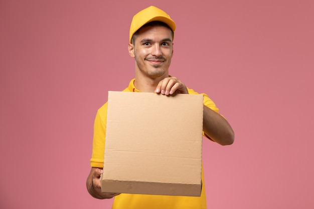Front view male courier in yellow uniform holding and opening food delivery box on pink background