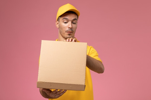 Front view male courier in yellow uniform holding and opening food delivery box on pink desk