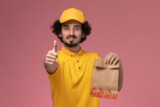 Front view male courier in yellow uniform holding paper food package posing on light pink wall