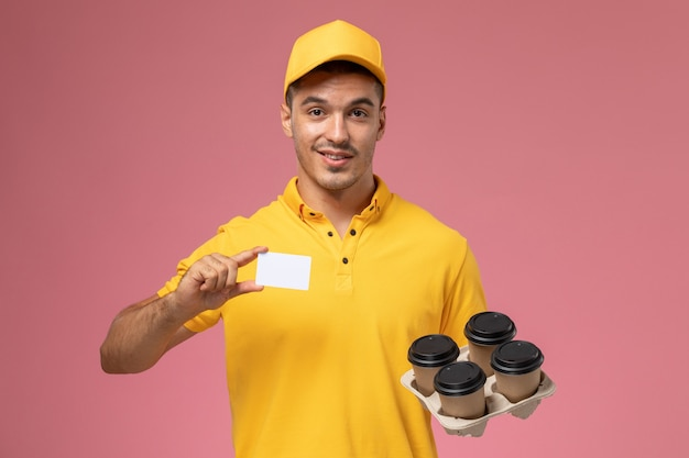 Front view male courier in yellow uniform holding plastic card and delivery coffee cups on the pink background