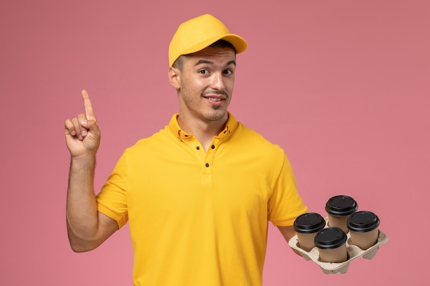 Front view male courier in yellow uniform smiling and holding delivery coffee cups on the pink