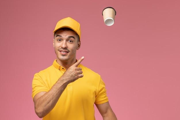 Corriere maschio di vista frontale in uniforme gialla che getta la tazza di caffè marrone di consegna sul rosa