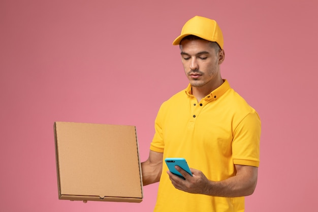 Front view male courier in yellow uniform using phone and holding food delivery box on pink desk