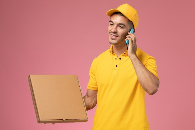 Front view male courier in yellow uniform using phone talking and holding food delivery box on pink desk