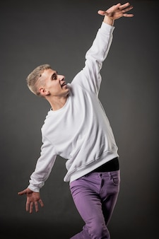 Front view of male dancer in purple jeans dancing