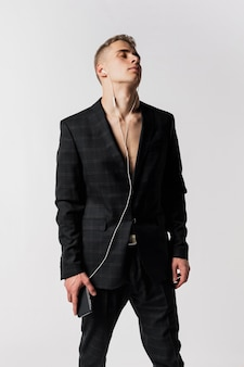 Front view of male dancer in suit enjoying music on headphones