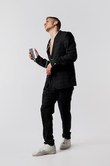 Front view of male dancer in suit and sneakers holding smartphone and headphones