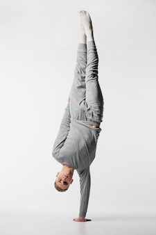 Front view of male dancer in tracksuit lifting his body on one arm